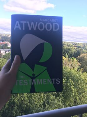 """Hand holding """"The Testaments"""" by Margaret Atwood with trees in the background."""