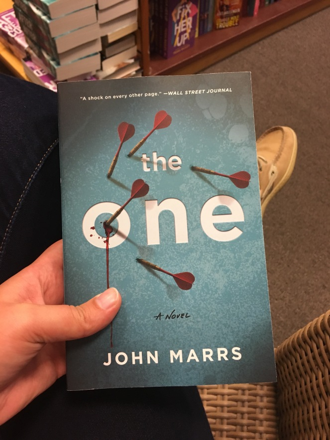 """A hand holding the book """"The One"""" by John Marrs with feet of the person in the background."""