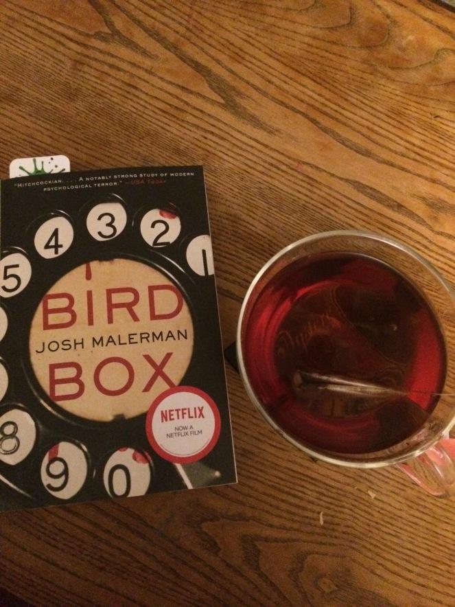 """Bird Box"" by Josh Malerman on a wooden table beside a cup of dark tea."