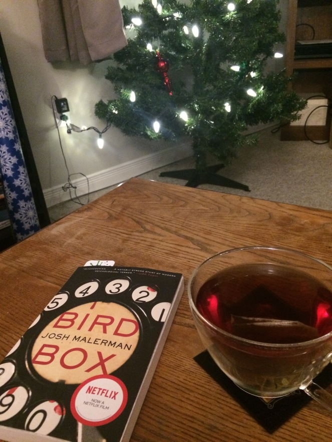 """""""Bird Box"""" by Josh Malerman on a wooden table beside a cup of dark tea with a fake Christmas tree in the background."""